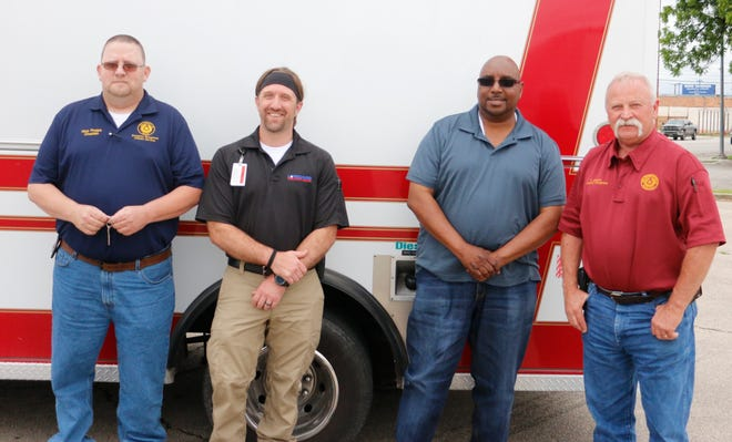 From left, Rick Phelps, Josh Chapman, Harold Hogan and Darrell Johnston are pictured with the vehicle previously used as an ambulance that American Medical Response donated to the Brown County Emergency Management Chaplain Services.