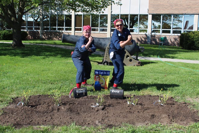 """Linda Rogers and Angie Morthland of the American Rosie the Riveter Association Cheboygan and Emmet Counties Chapter planted a rose garden on the lawn of the Cheboygan County Building the morning of May 27. Each plant is in honor of a woman who worked as a """"Rosie the Riveter"""" during World War II."""