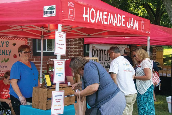 Customers shop at Holly's Heavenly Jam booth during the Fresh Finds Adel Farmer's Market in 2020.