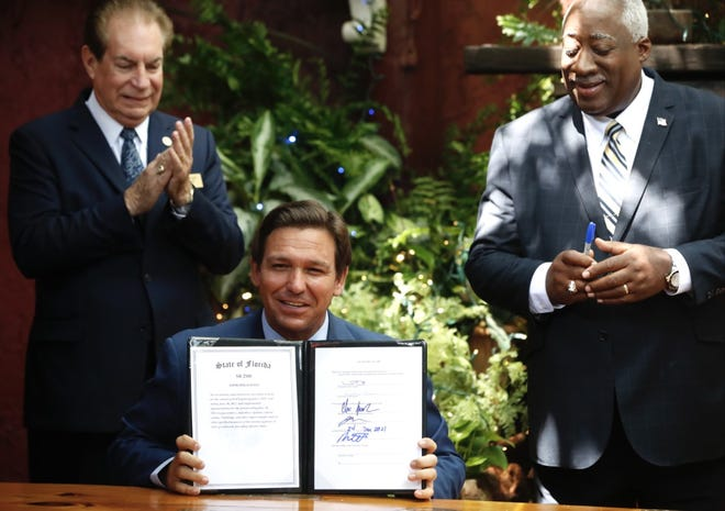 Gov. Ron DeSantis shows the signed 2021-22 state budget he had just signed Wednesday in New Smyrna Beach. State Sen. Tom Wright, left, and state Rep. Webster Barnaby, right, applaud.