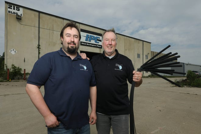 Jason Ciudaj and his father, Jeff, hold a handful of Deep Root Irrigation units, which the two developed together, Wednesday outside their West Burlington Deep Root Irrigation LLC, facility. The Deep Root Irrigation system is intended to deal with declining water availability in California's agricultural valleys. The company will manufacture an irrigation system for olive trees, vineyards and a wide variety of fruit- and nut-bearing trees that allows water to be introduced directly to the plant's root system. This methodology will reduce water consumption for the crops.