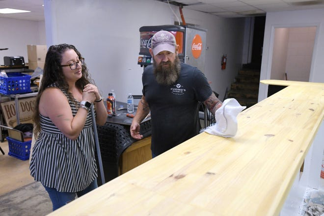 Christopher Condon wipes down the newly refurbished bar while Caitlin Zalmanoff sweeps as they renovate a former diner space Tuesday, June 1, into what soon will become The Southern Italian deli and market, a New York-style deli with a Southern twist.