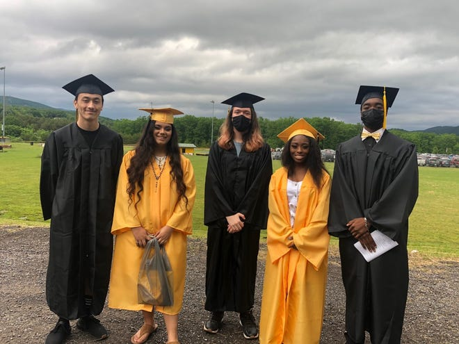 Damian Rhett Thongdara, Alexis Torres, Colton Turner, Delta Wheeler and Henderson Joshua Wheeler hang out as they await the start of the procession into Alumni Field Sunday for Keyser High School's graduation.