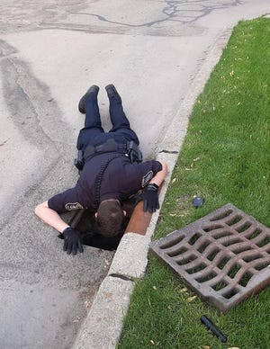 Monroe Police Officer Peyton Smithers removed a sewer grate, laid down on Bentley Drive and saved a duckling that fell into the sewer.