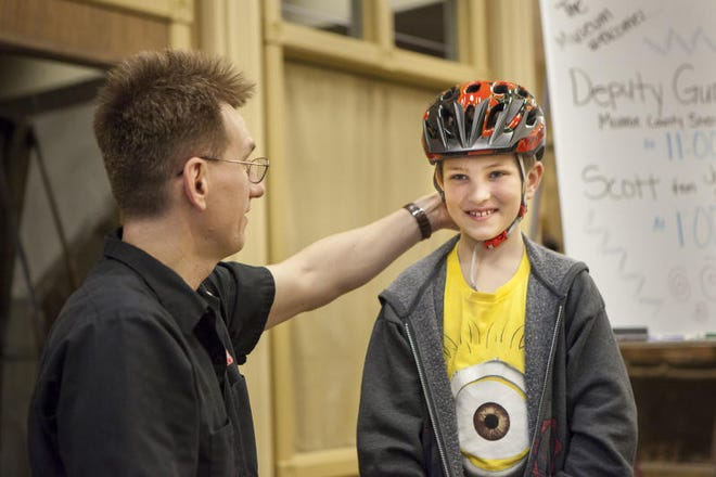 """Scott Goocher from Jack's Bicycles talks about helmets with Henry Doom, then 8, in this 2015 photo. Goocher will teach """"Bike 101"""" June 9 at St. Paul's United Methodist Church."""