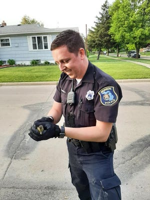 Monroe Police Officer Peyton Smithers is all smiles after rescuing a duckling that fell between the quacks and into a sewer on Bentley Drive. Local residents Bill and Norma Huntley noticed Officer Smithers laying on the pavement. He later said he was patrolling on Bentley Drive when he saw a mother duck waddling down the street with her ducklings following. He saw one of the ducklings fall into the sewer while the mother duck continued on, not noticing one of her babies was missing. In an attempt to retrieve the duckling from the sewer, Officer Smithers removed the grate cover and lay down on the street, reaching for the duckling. Meanwhile, the Huntley's daughter, Lisa Huntley Sheets, who was visiting from Lambertville, went to get a rake to help. When she returned, she found the officer had already scooped the duckling up from the sewer in one fowl swoop. She reported the smile on Officer Smithers' face was priceless and his effort should be a nice feather in his police hat. He reunited the duckling with its family and determined there was no fowl play.