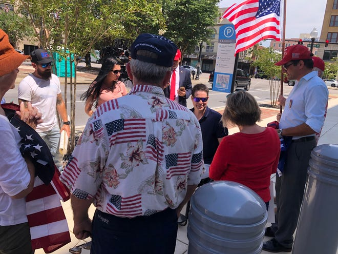 Brian Kolfage (center) is surrounded by supporters Wednesday following his arraignment in federal court in Pensacola, where he pleaded not guilty to federal tax charges.