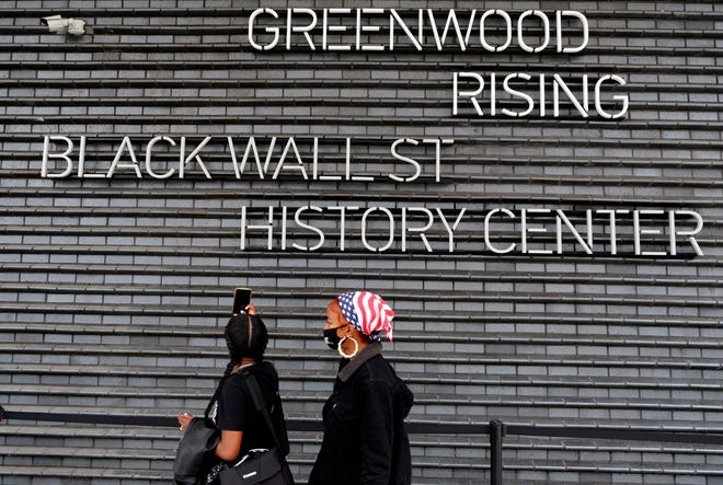 """Two descendants of Tulsa Race Massacre survivors prepare to walk into the """"Greenwood Rising: Black Wall Street History Center"""" after an open-air dedication ceremony on Wednesday at Greenwood Avenue and Archer Street in Tulsa."""