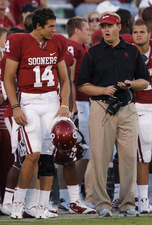 Josh Heupel (right) talks to Oklahoma quarterback Sam Bradford during a 2008 game in Norman. Heupel, then the Sooners quarterback coach, is one of five former players with state ties on the 2022 College Football Hall of Fame ballot. Heupel quarterbacked the Sooners to a national championship.
