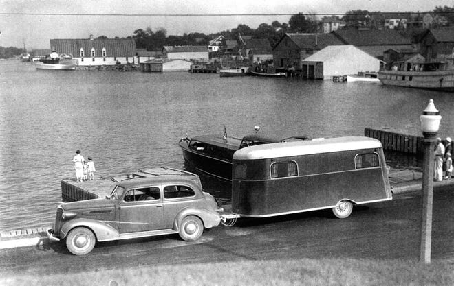 A car is seen hauling a camper in a time when parking was allowed on the Round Lake waterfront