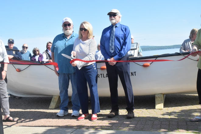 Tammie LaPointe (center), the granddaughter of former chief engineer Irvin Wendorf, cuts the ceremonial ribbon at the unveiling of the refurbished J.B. John lifeboat Wednesday at the Petoskey Waterfront A Pier. Captain Lon Calloway of Indian River (left), who restored the vessel in 1997 spent close to five weeks again restoring the historical boat, while at right is Petoskey mayor John Murphy.