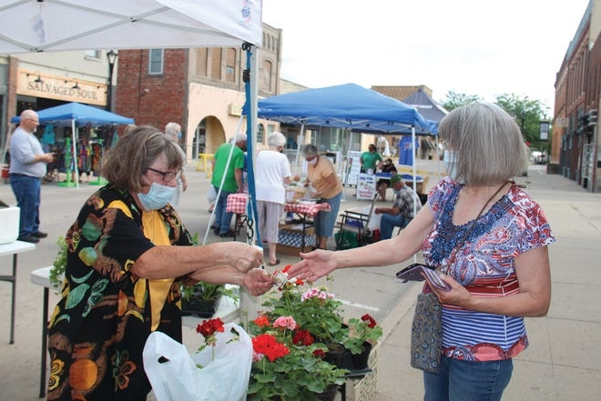 Deb Carter, of Hidden Acres in Coon Rapids, gives change back to Kathy Miller during the 2020 Perry Farmers Market.