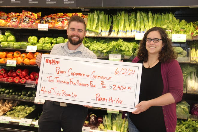 Hy-Vee Store Manager Eric Doughan presents a check to Perry Chamber of Commerce Executive Director Lynsi Pasutti at the end of the round-up event for the Fourth of July Fireworks Drive.