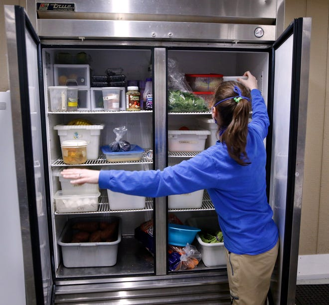 Rebecca Hollenbeck looks for ingredients in the commissary's fridge. Most of the food is stored in large walk-ins. With 800 animals to feed multiple times a day, there are many spaces designated for fresh food storage.