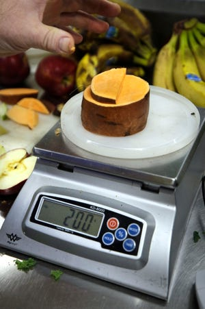 Pieces of sweet potato are weighed on a scale to create food portions for one of the many animals at the RWP zoo.
