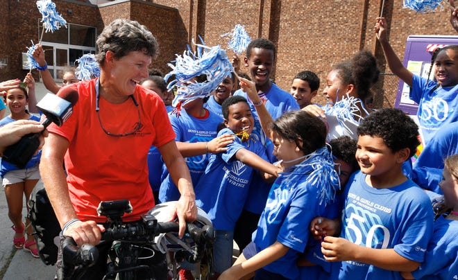Judy Davis greets kids from the Fox Point Boys & Girls Club of Providence after making her final stop in her cross-country bicycle trip in 2018.