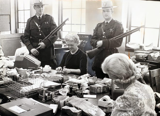In 1963, cash was pouring in at the RI Department of Motor Vehicles on the final date for car registrations to be submitted. DMV employees Dorothy Cull, right, and Emily Paquin were guarded by state Troopers Dennis Tabor and John Reise, who carried loaded shotguns.