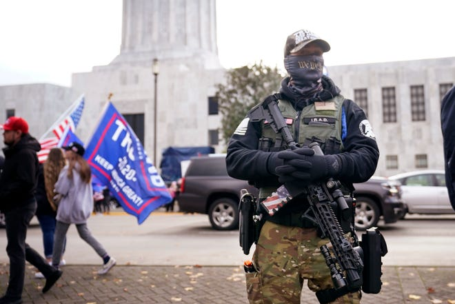 A man holds a gun as he stands in front of the Oregon State Capitol building in Salem, Nov. 7, 2020. Gov. Kate Brown signed a bill Tuesday that bans guns from the Oregon Capitol, changing a law that allowed concealed handgun licensees to bring firearms into the building.