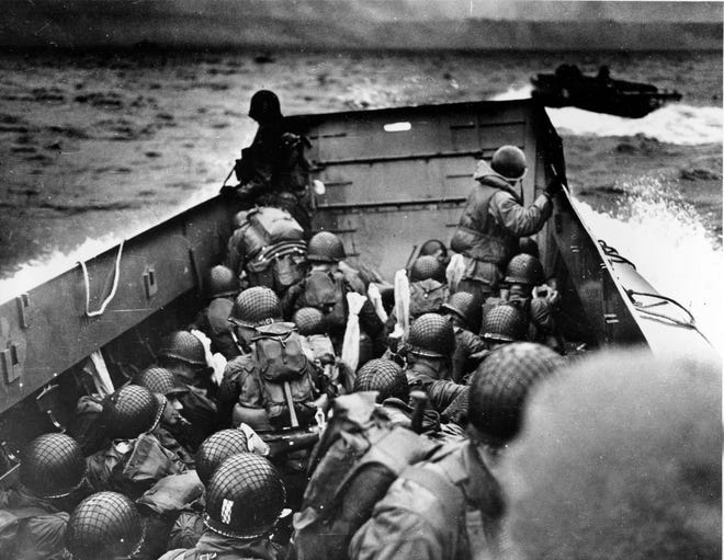 In this photo provided by the U.S. Coast Guard, a U.S. Coast Guard landing craft, tightly packed with helmeted soldiers, approaches the shore at Normandy, France, during initial Allied landing operations on June 6, 1944.