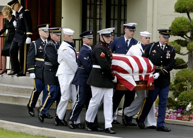 A military honor guard carries the casket of former President Ronald Reagan as Nancy Reagan, back left, is escorted by Maj. Gen. Galen B. Jackman, as they leave a funeral home in Santa Monica, California, on June 7, 2004, to escort Reagan's casket to the Reagan Library. Reagan died on June 5, 2004.
