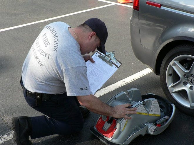 Wilmington firefighter helps install baby car seat.