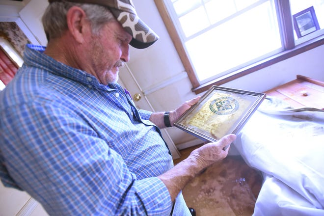 Ervin Ezzell looks at a picture frame with his lifetime N.C. hunting and fishing license after floodwater damage to his home off Heading Bluff Road in Currie, N.C. Oct. 19, 2016.