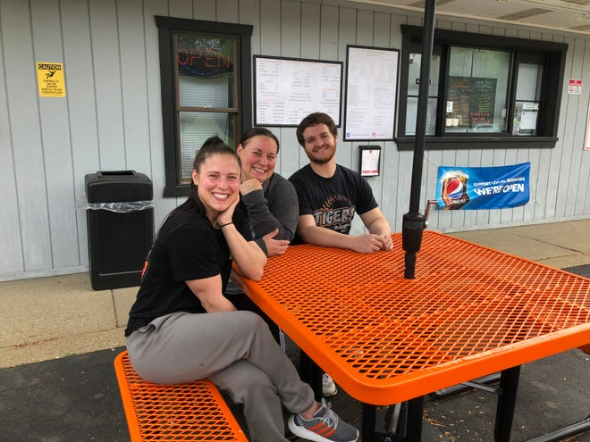 Ashley, Trenda and Devin Aul sit at the new orange and black tables at The Burg Grill and Creamery in Strasburg.