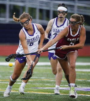 DeSales junior midfielder Gianna Cua (left) battles Watterson's Brooke Biagi for possession during the Division II, Region 7 final May 28. The host Stallions lost 10-9 to finish 14-7. Cua finished the season with 61 goals.
