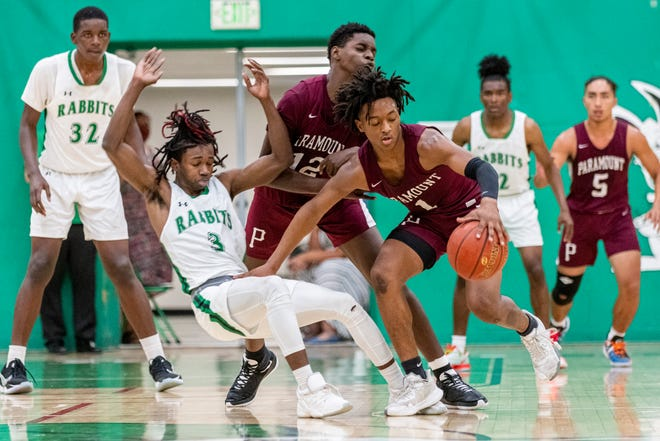 Victor Valley's Eric Redic gets knocked down by Paramount's Marques Calcote during their CIF-Southern Section quarterfinal playoff game in Victorville on Tuesday. Victor Valley lost 75-59.