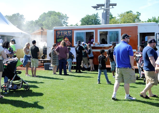 Customers line up for barbecue at the Fire & Smoke BBQ truck at the Evansville Food Truck Festival on Sunday, May 30, 2021.