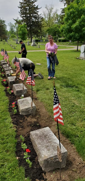 Marion Elks Lodge 32 Members Dave Feliciano, Rex Coldwell and Amber Lowther clean the area around the eight gravesites included in the Elks Rest in the Marion Cemetery.