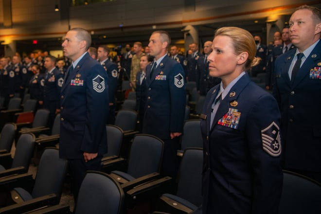Graduates of Class 21-E stand for the arrival of the official party at a graduation ceremony at the Senior Noncommissioned Officer Academy on Maxwell-Gunter Annex, Alabama, May 26, 2021. The SNCOA held its first in-person graduation ceremony since the World Health Organization declared COVID-19 a pandemic in March 2020.