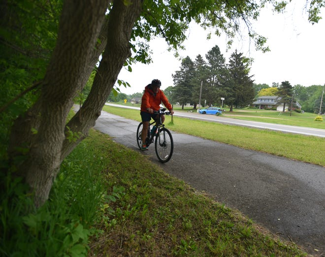 A cyclist uses the Huron Valley Trail north of I-96 near New Hudson on June 2, 2021.