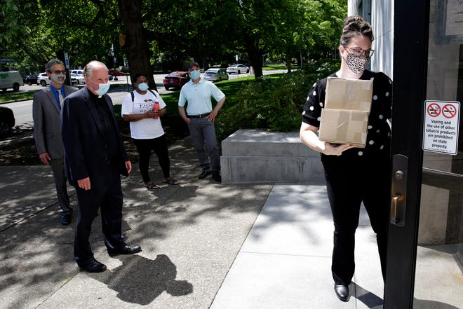 An employee with the Oregon Secretary of State's office takes boxes containing signatures for initiative petitions 17 and 18 from the petitioners inside the Oregon Public Service Building on Wednesday, June 2, 2021