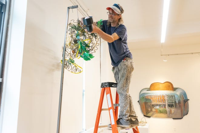 Artist Brian Smith adjusts his entry in the Strong and Unusual exhibition at the Pioneer School Community Arts Center.