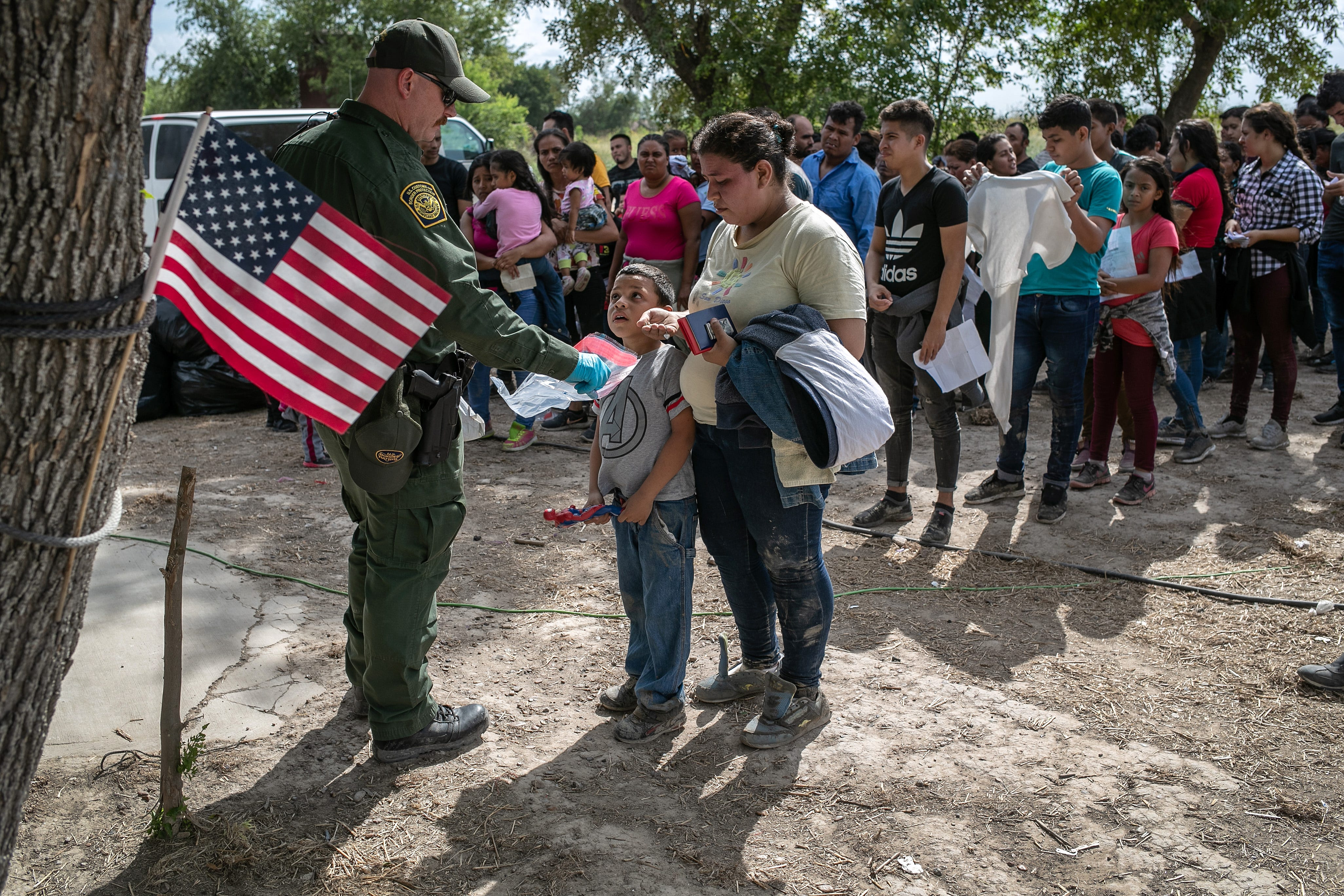 A U.S. Border Patrol agent gathers personal effects from immigrants July 2, 2019, in Los Ebanos, Texas, before they are transferred to a processing center in McAllen.