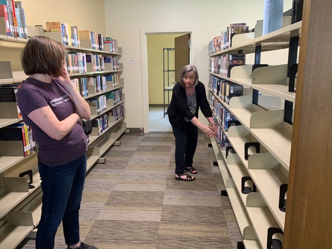 Kristi Floyd, left, and Mary Jo Finch discuss the best way to shelve books at the Westbank Community Library. The library sustained damage during the winter freeze and underwent months of repairs.