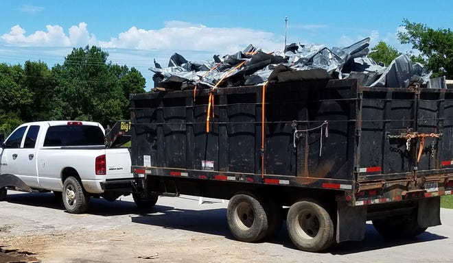 The remains of the Red Rock General Store's roof, which was damaged and ripped off during severe storms on May 28, is hauled away.