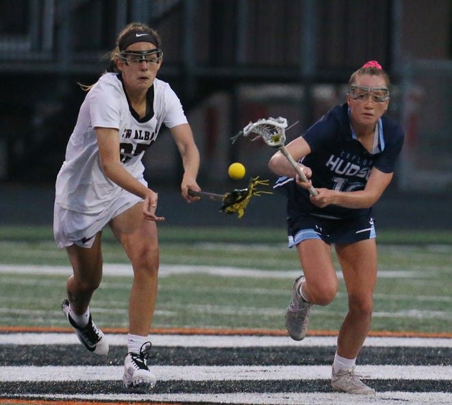 New Albany's Abby Cole and Hudson's Emily Ritenour battle for the ball in the second half of the Explorers' 12-6 loss in a Division I lacrosse state semifinal at Green High School on Wednesday night. [Mike Cardew/Beacon Journal]