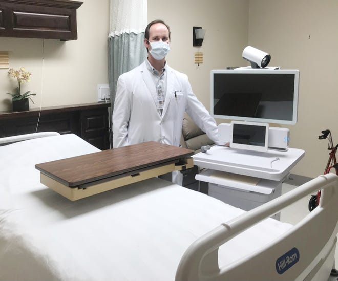 Dr. Sam Franklin poses in a patient room at Jefferson Hospital with the telemedicine cart used to consult bedside with specialists at Augusta University Medical Center.