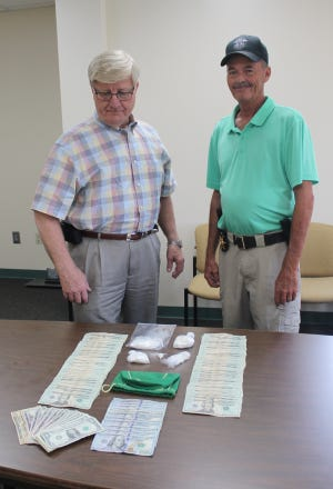 Jefferson County Sheriff Gary Hutchins (at left) stands with one of his deputies, Sgt. Tim Frawley (at right). The sheriff is looking over the cash and drugs discovered after Reco Cooper was stopped for not wearing a seatbelt. The items were found in his possession. Cooper faces several charges including trafficking in cocaine.