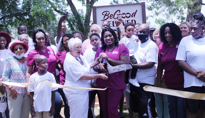 Paula Stickle, former owner of Paula's Home Place, and Ashley Kitchens, the new owner of BeGood-BeLoved stand side-by-side while cutting the ribbon on the newly re-branded personal care home in Louisville.
