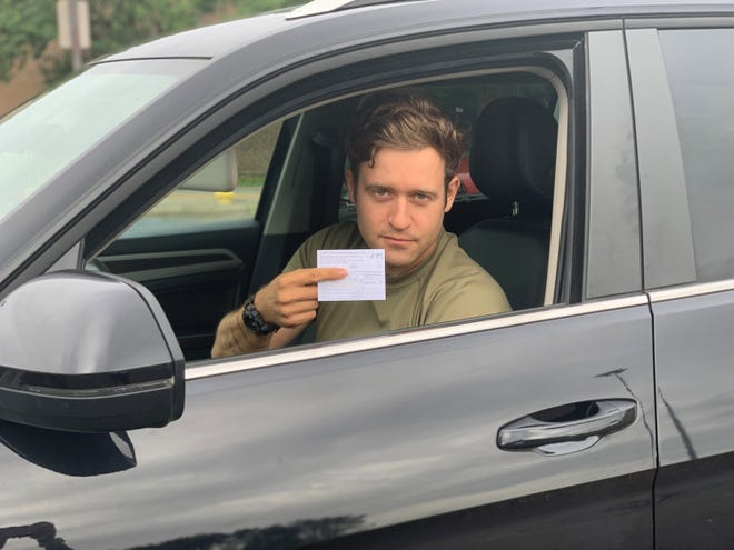 Staff Sgt. Ethan Shjamdemaar, 2nd Battalion, 2nd Infantry Regiment, 3rd Brigade Combat Team, 10th Mountain Division, displays his vaccination record after being the first person vaccinated during the drive-thru COVID-19 vaccination event on May 22.