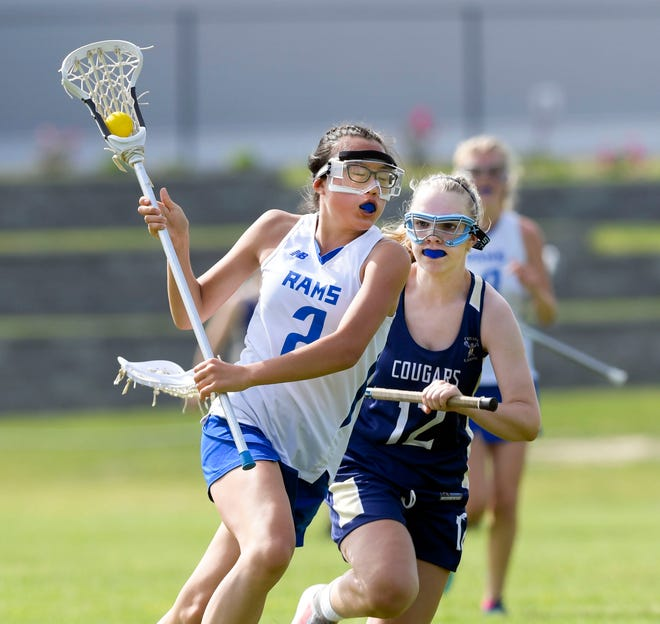 Meredith Conner of Upper Cape drives with Annie Yeaton of Tri County in pursuit in a lacrosse game Wednesday, won by Upper Cape.