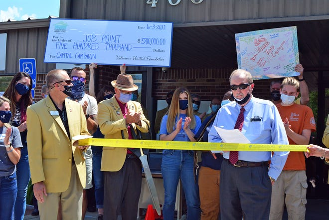 Job Point President and CEO Steven A. Smith, right front, reads a statement Thursday about the job training facility's ability to purchase its building at 400 Wilkes Blvd. thanks to donations from Veterans United Foundation as part of a ribbon-cutting ceremony.