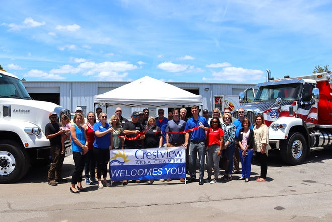 """Flanked by a pair of Autocar """"severe-duty"""" trucks and surrounded by members of the Crestview Area Chamber of Commerce, Southern Commercial Diesel owner Kyle Ramos cuts the ribbon opening his Lloyd Street diesel truck maintenance and repair business recently in Crestview."""