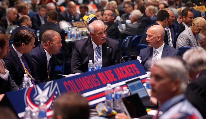 Recently re-hired Blue Jackets President of Hockey Operations John Davidson, center, and general manager Jarmo Kekalainen, right, will again join forces for the 2021 NHL draft to be held virtually July 23-24. The Blue Jackets own the fifth overall pick, which they learned Wednesday after the NHL's draft lottery.