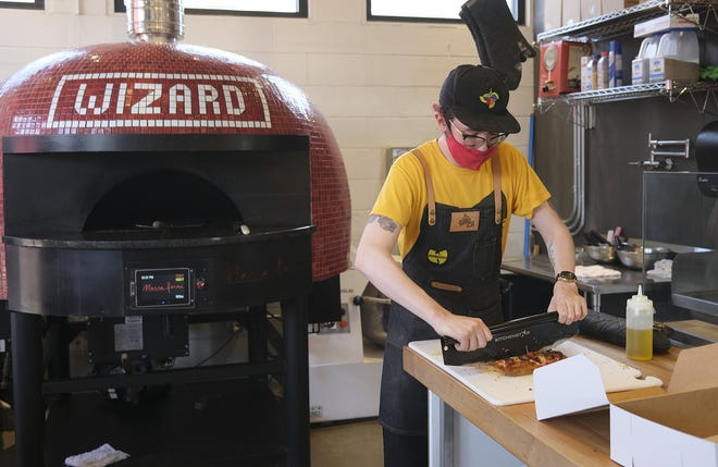 Dylan Jones slices up pizzas at Wizard of Za in Clintonville.