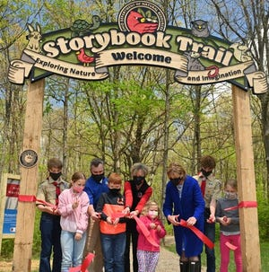 First Lady Fran DeWine (pictured in the blue coat) participates in a ribbon cutting at Findley State Park's Storybook Trail.