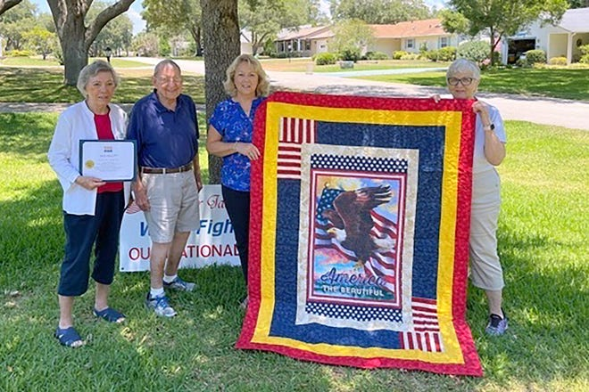 B.J. Hauserman, Pam Beightol and Joan Leubbers of the Ocklawaha Chapter of the Daughters of the American Revolution present the Quilt of Valor to Major Jack Hallett.